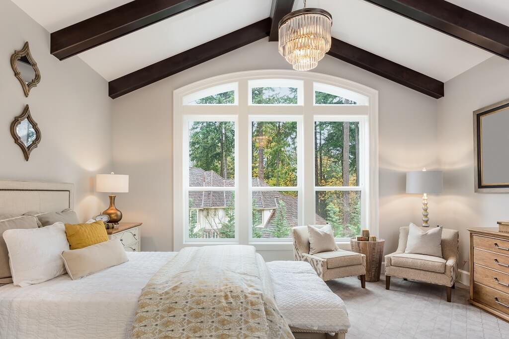 Beautiful furnished master bedroom interior in luxury home . Features vaulted ceiling with wood beams and chandelier.