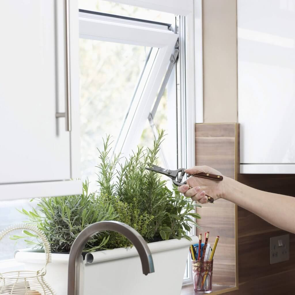 An opened awning window above a kitchen sink