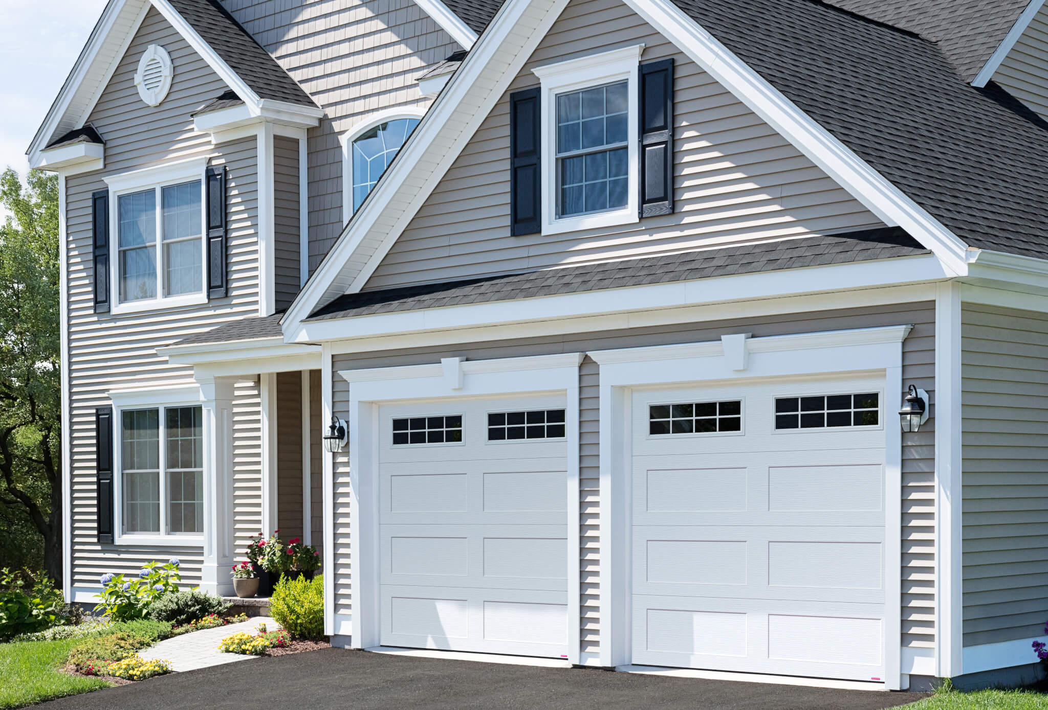 a grey house with double white garage doors