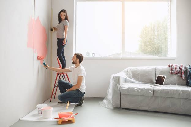 Couple Painting a Wall Near a Window