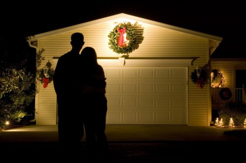 a couple admiring their garage door decorated with a wreath